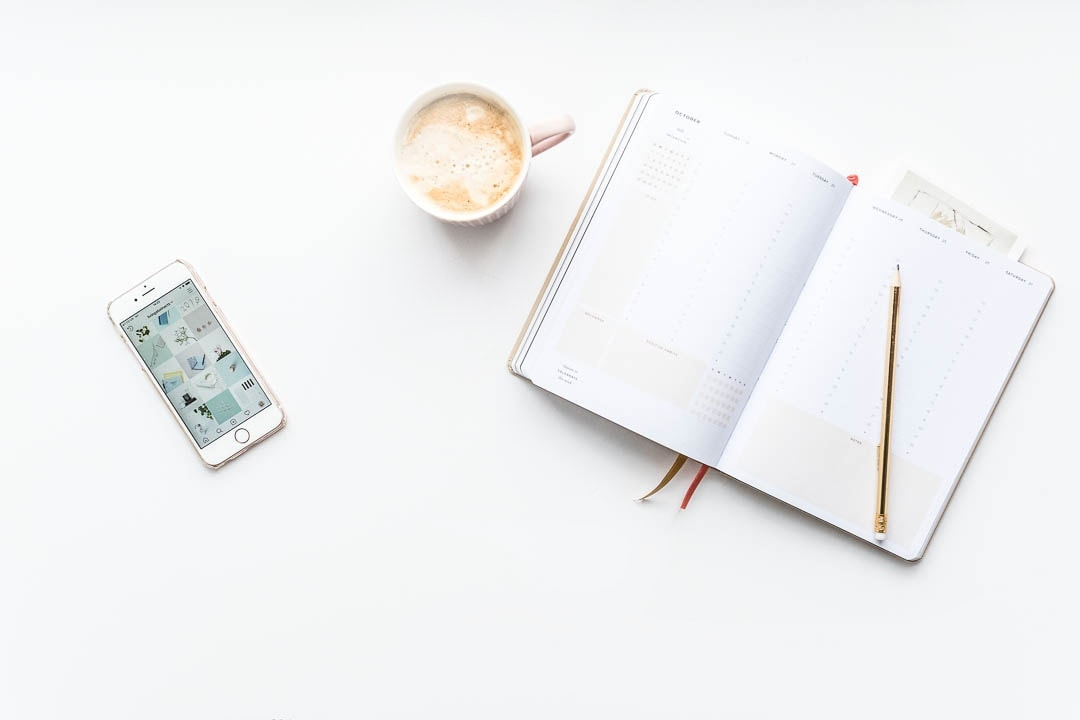 Reasons to use a social media scheduler - including peace of mind with this Ponderlily planner, Instagram app on an iPhone and a delicious coffee in a pink mug.